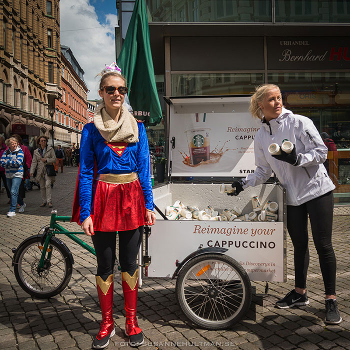 Tjej utklädd till Stålkvinnan bredvid vagn med kaffe
