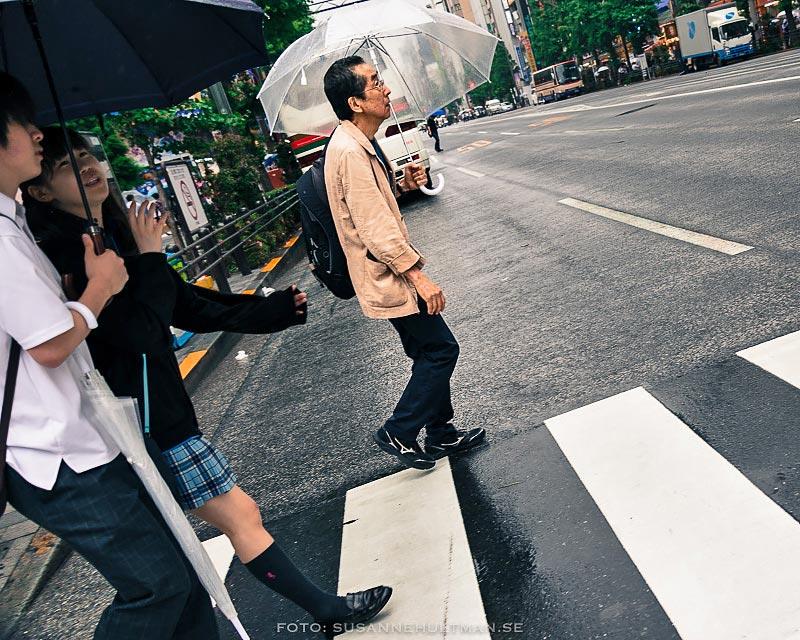 Man med paraply på övergångsställe