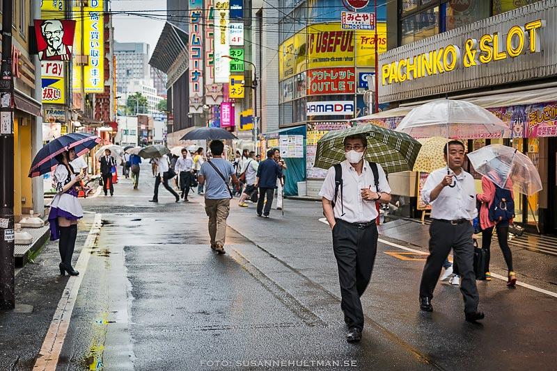 Män med paraplyer på en gata