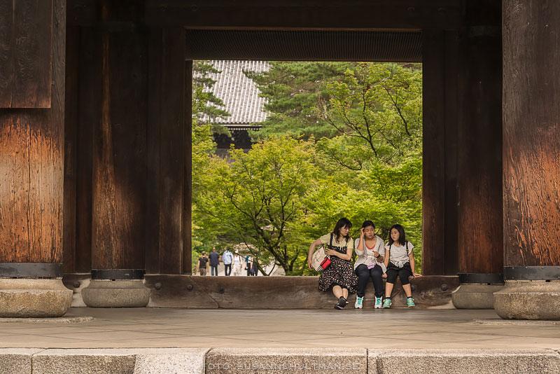 Tre flickor sitter vid Nanzenjitemplets port