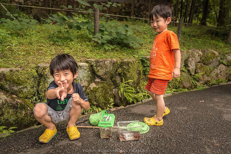 Två glada pojkar med kräftfångst i burkar