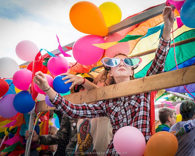 Glada människor med ballonger på lastbilsflak