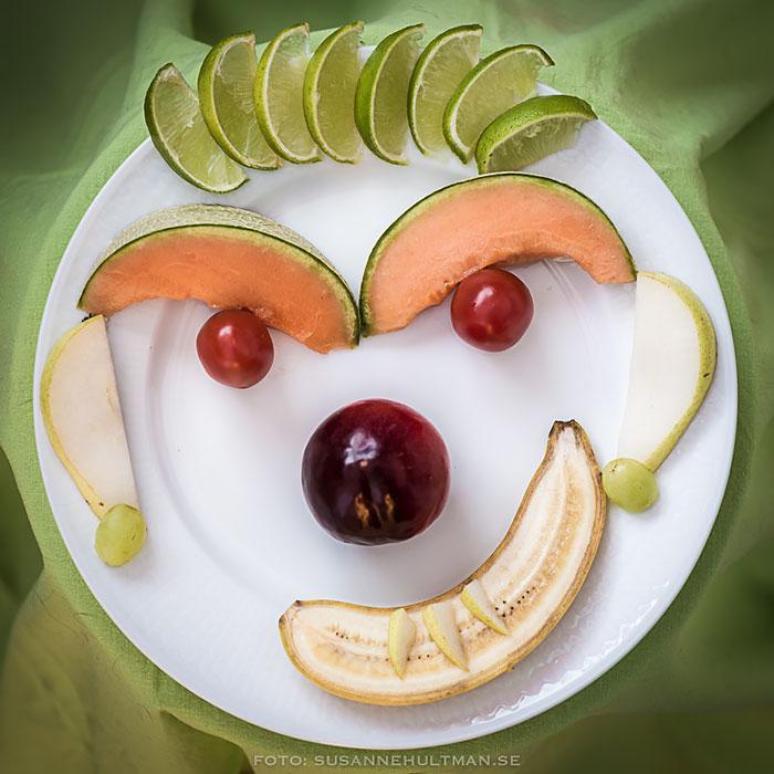 Tallrik med frukter placerade som ett ansikte