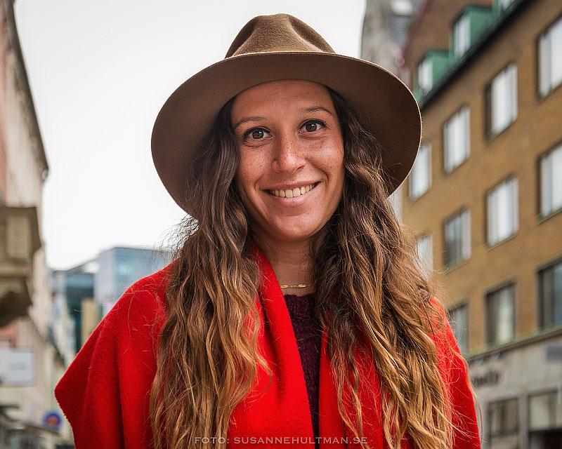 Glad kvinna i hatt och röd kappa