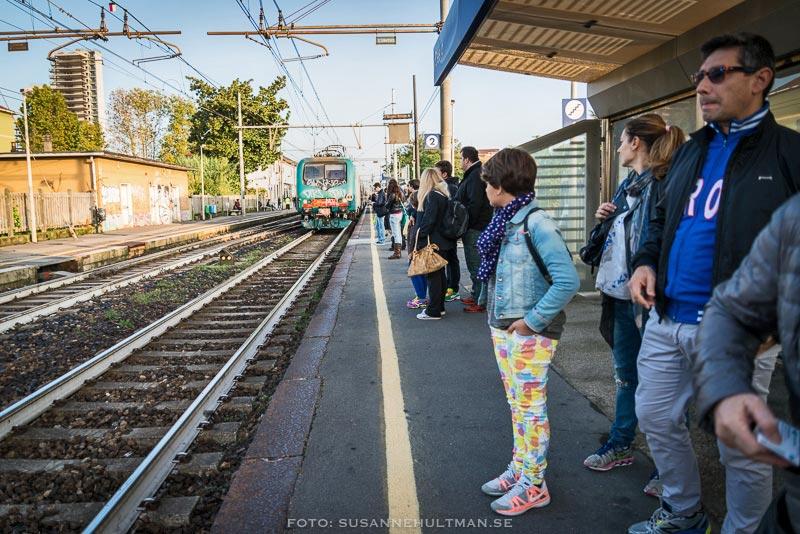 Tågperrong med tåg på väg in.