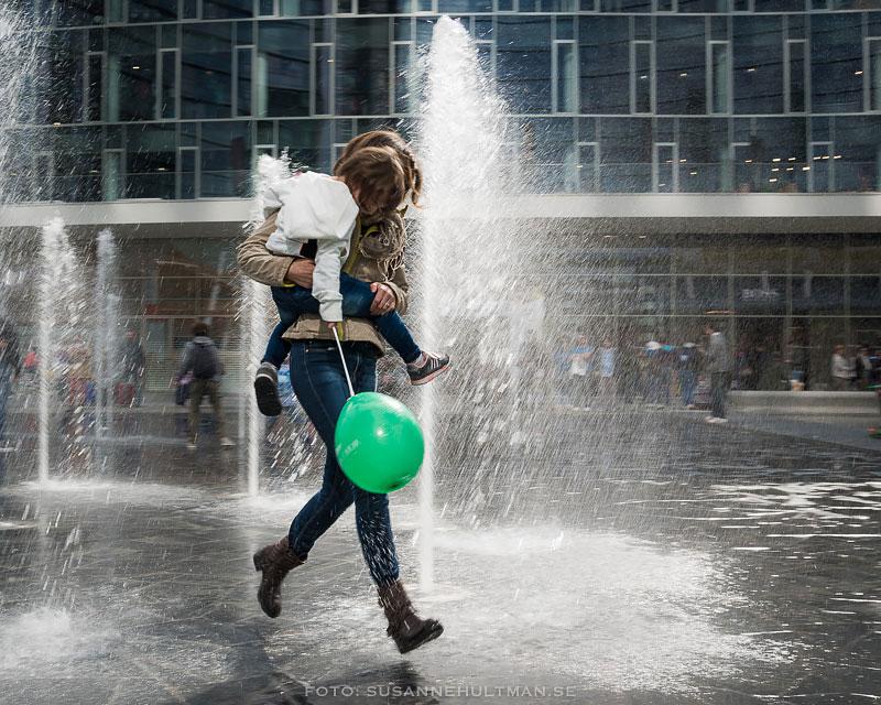 Mamma med barn i famnen och grön ballong i handen vid fontän
