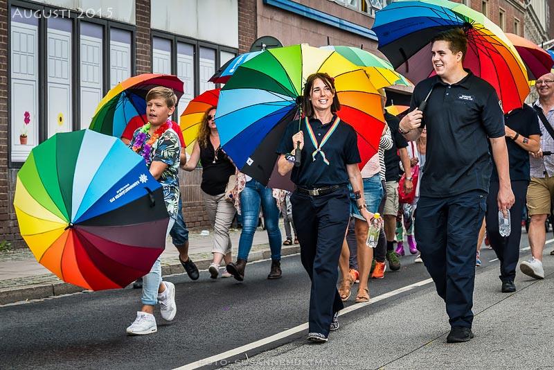 Pridedeltagare med regnbågsparaplyer