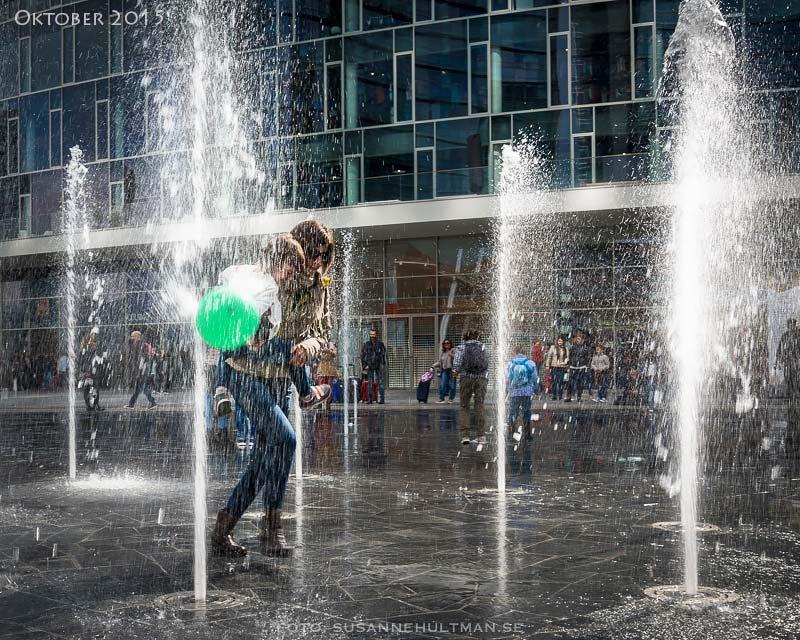 Kvinna med barn och grön ballong i vattenfontän