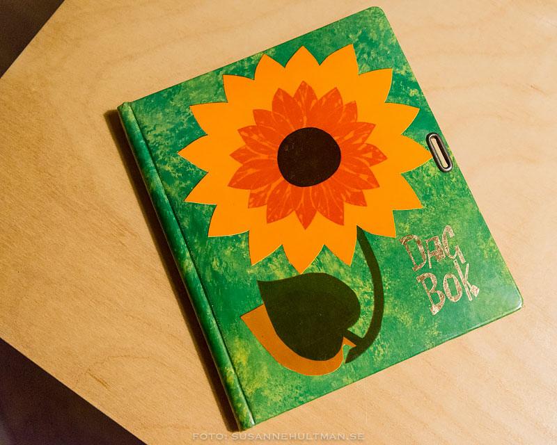 Grön dagbok med orange blomma på omslaget