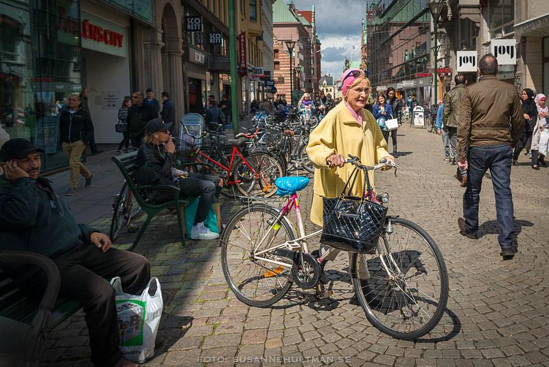 Dam klädd i rosa schalett leder cykel
