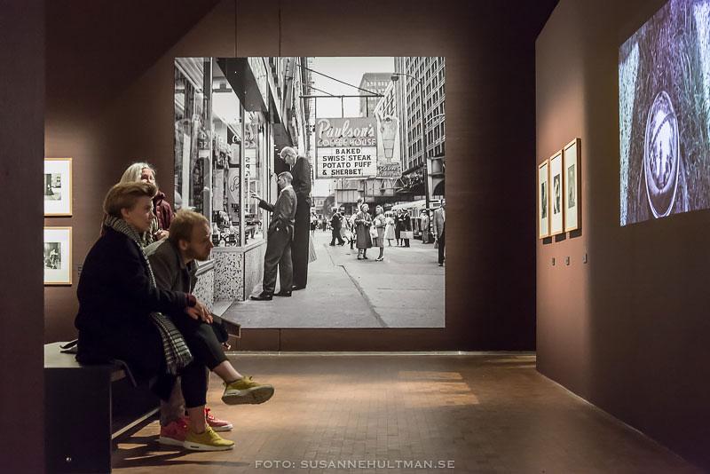 Personer på bänk tittar på film om Vivian Maier