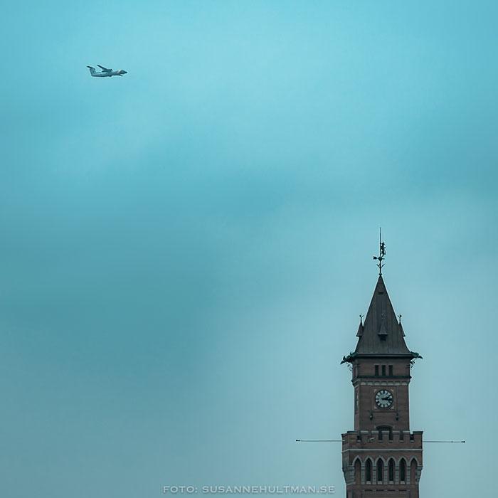 Flygplan och kyrktorn mot blåfärgad himmel