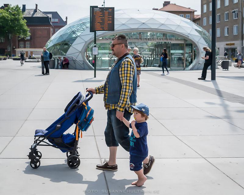 Man med barnvagn och barfota pojke