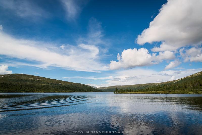 Klarblå himmel speglar sig i sjön