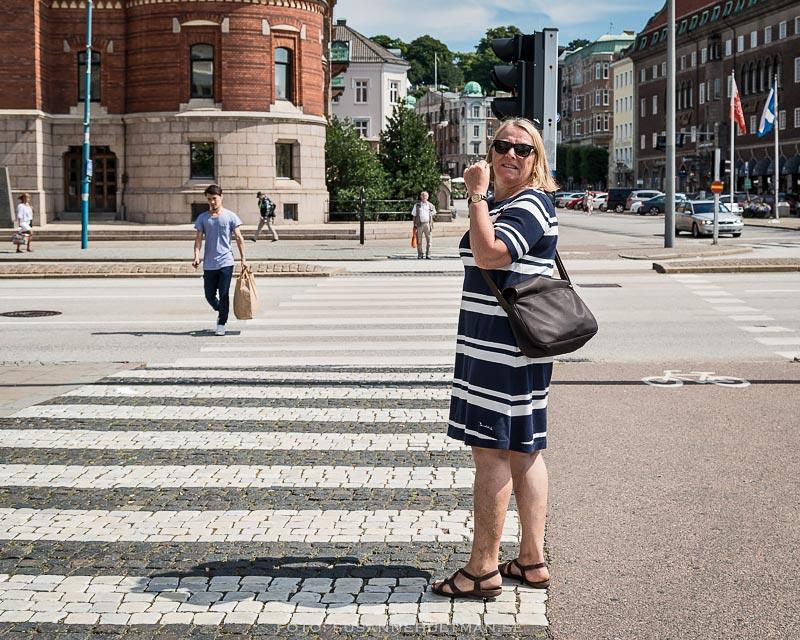 Kvinna iklädd randig klänning stående vid övergångsställe