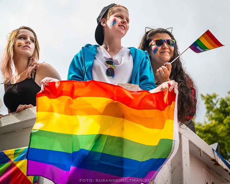 Tre tjejer med regnbågsflaggan