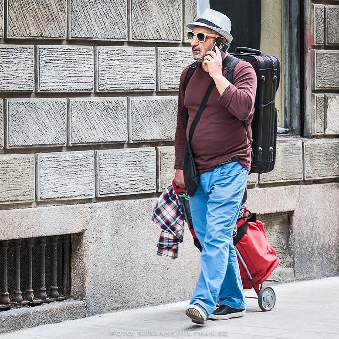 Man med resväska och mobil.
