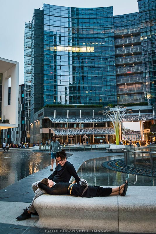Par vid fontän och skyskrapor