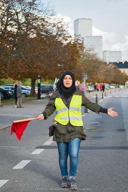 Kvinna i gul väst och med röd flagga