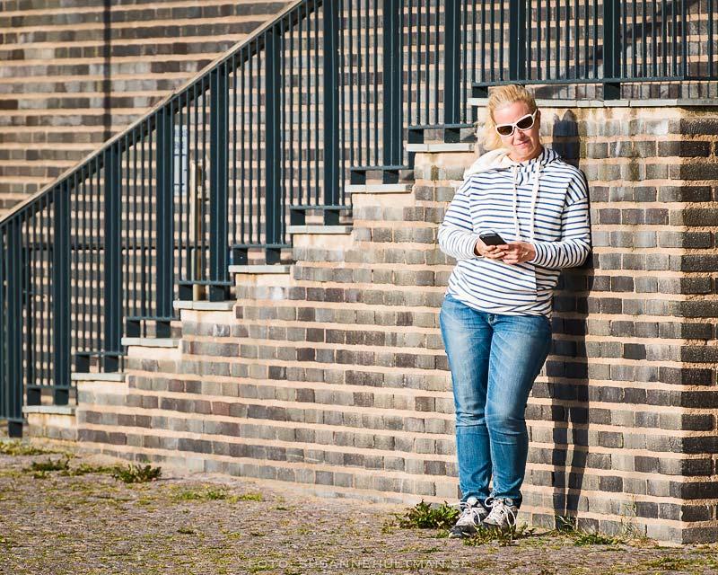 Kvinna med mobil vid solig vägg