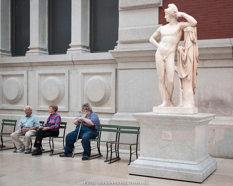 """Skulptur som """"tittar"""" på personer på en bänk."""