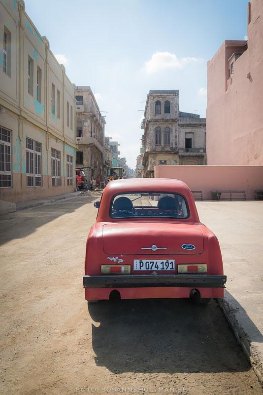 Röd gammal bil på gata