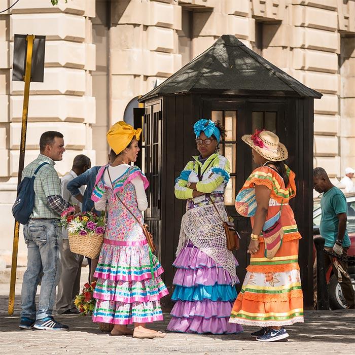 Tre kvinnor i färggranna klänningar