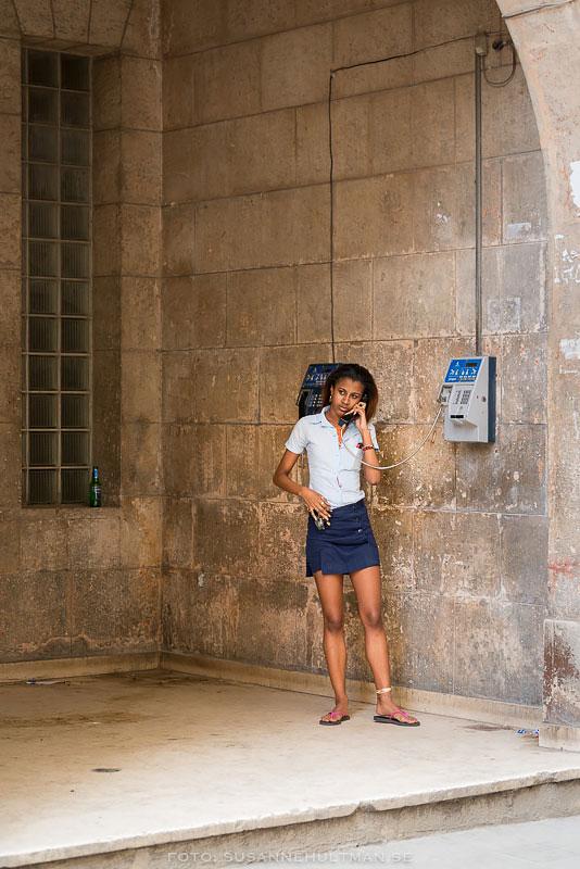 Flicka vid offentlig telefon