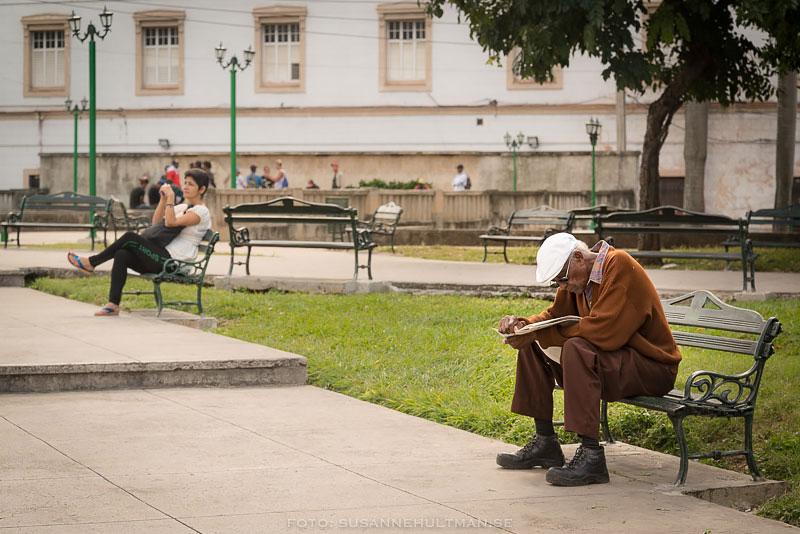 Man på bänk läser tidningen