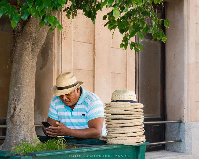 Man med mobil säljer hattar