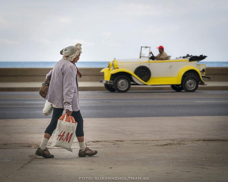 Kvinna med plastkasse från H&M och veteranbil i bakgrunden