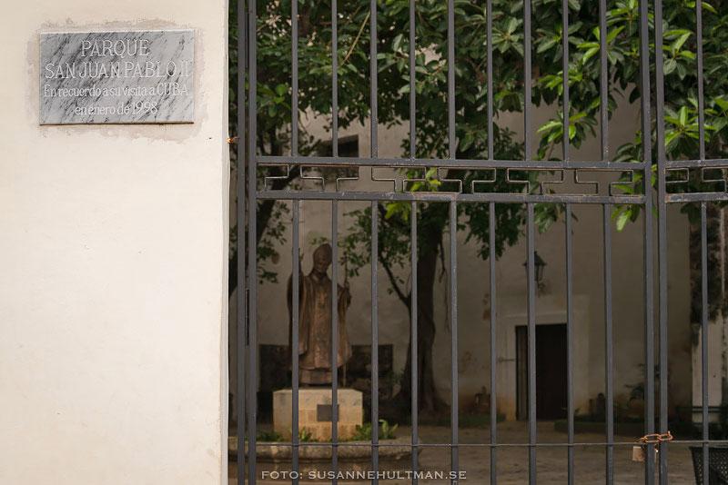 Staty av Johannes Paulus innanför stängd grind