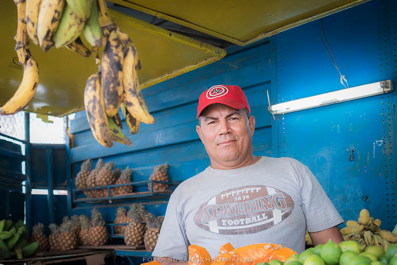 Försäljaren med bananer hängande bredvid