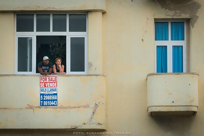 Till salu-skylt i ett fönster med två personer