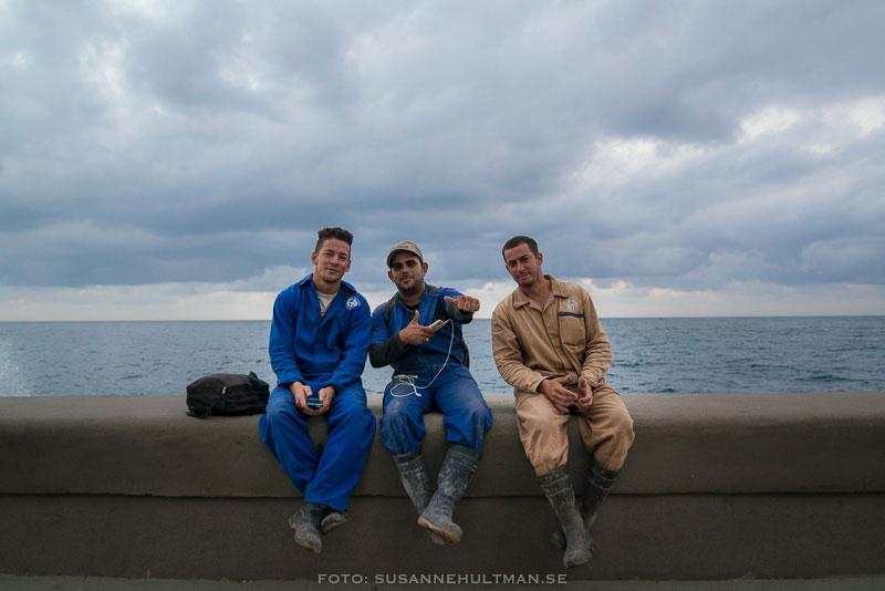 Tre män vid Malecón