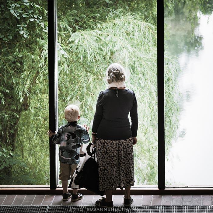 Kvinna med barn tittar ut genom ett fönster