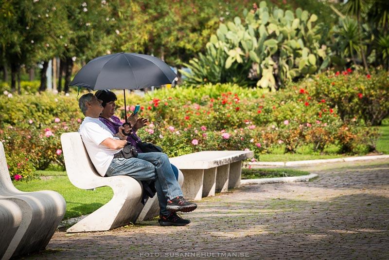 Par på bänk med paraply som skydd för solen