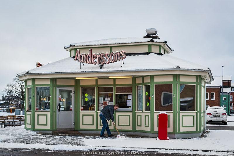En man skottar snö framför Anderssons korvkiosk