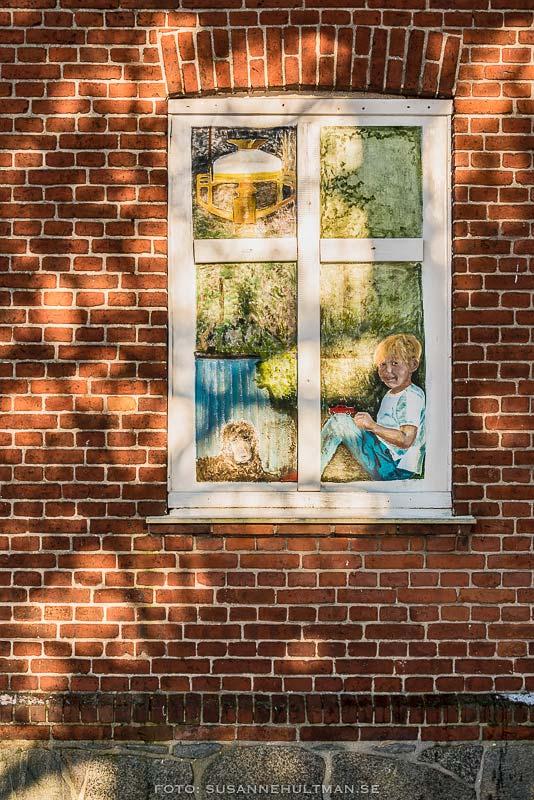 Målat fönster på tegelvägg.