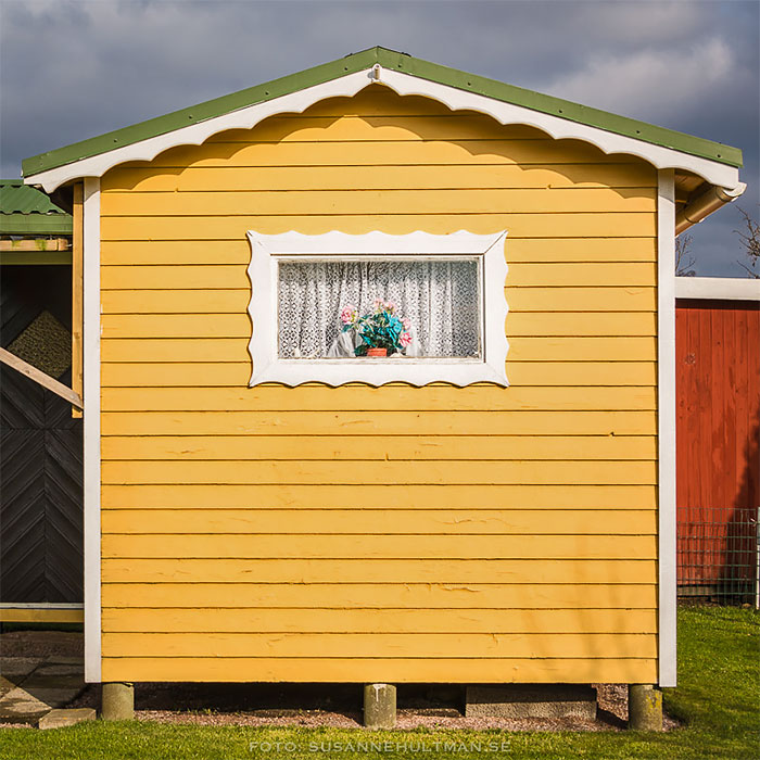 Gul kolonistuga med litet fönster
