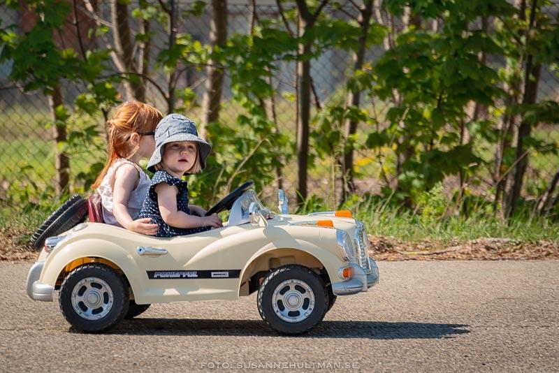 Vit liten bil med två barn