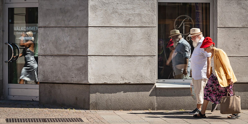 Ett äldre par speglas i ett fönster och en ensam kvinna speglas i en glasdörr