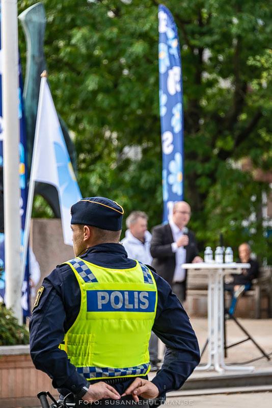 Ryggen på polis och längre bort en talare i talarstol
