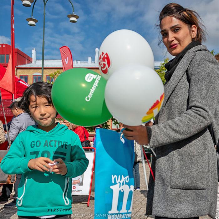 Pojke och kvinna med partiballonger och tygkasse.
