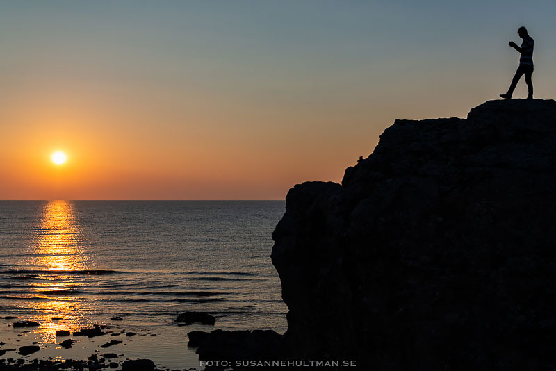 Silhuett av man på klippa med solnedgång över havet i bakgrunden.