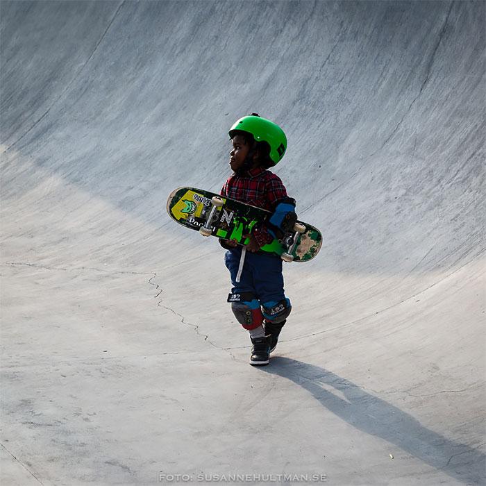 Pojke med skateboard i famnen