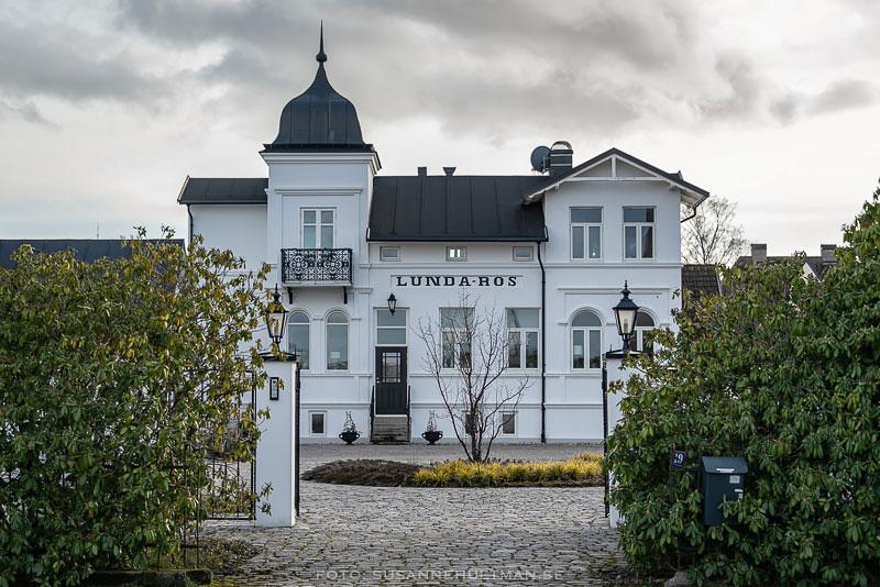 Villan Lundaros i vitt och med svart tak och torn.