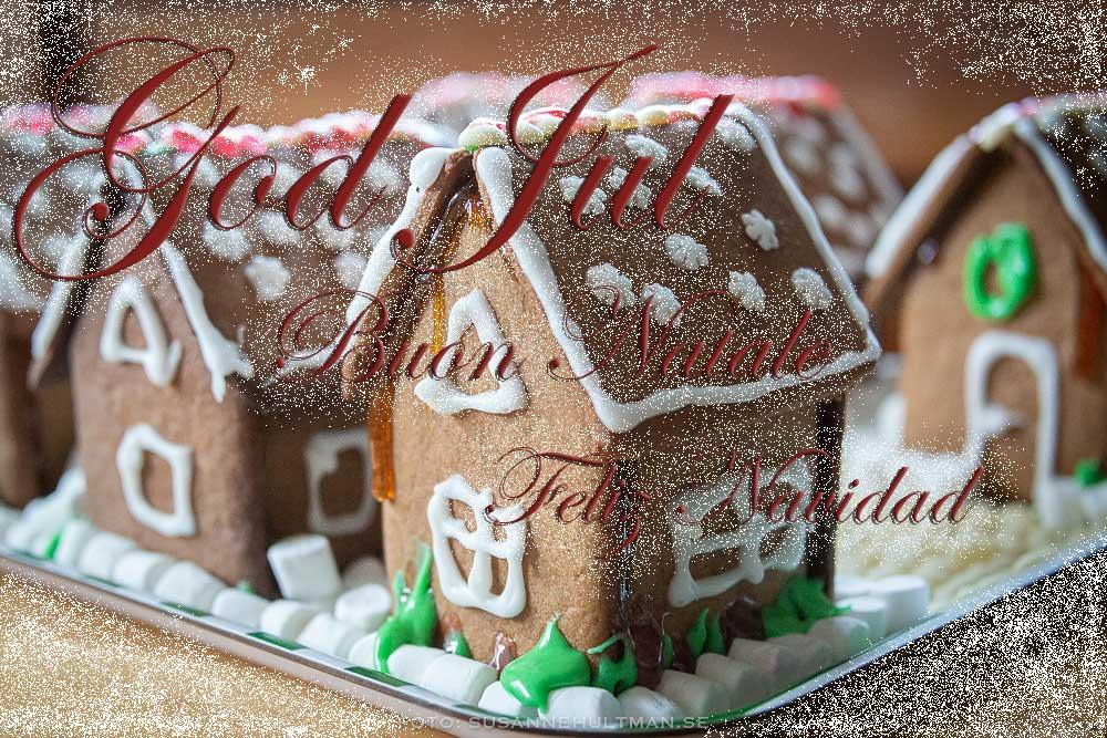 Dekorerade pepparkakshus med julhälsning på svenska, italienska och spanska