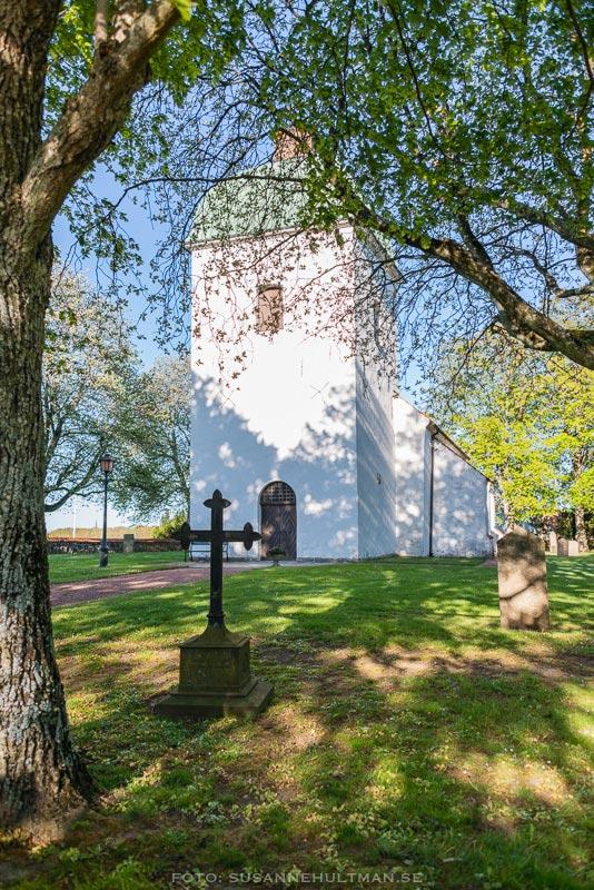 Västra Sallerups kyrka med kors framför och inramad av grönskande träd.