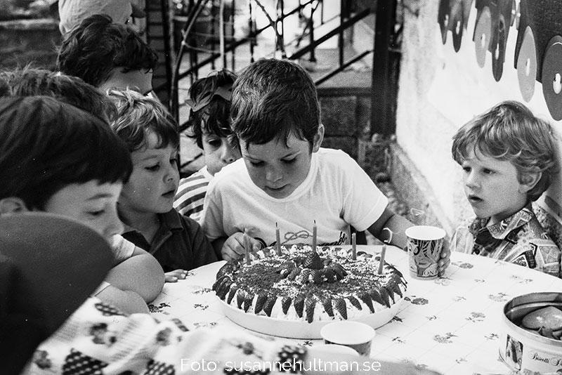 Sonen omgiven av kamrater blåser ut fem ljus i tårta.